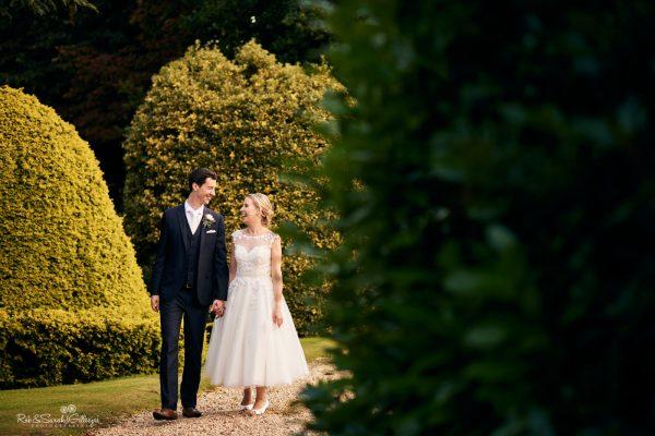 Bride and groom walk through topiary garden at Highbury Hall