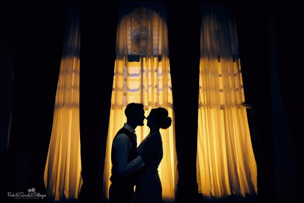 Silhouette of bride and groom against brightly lit window at night