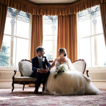 Bride and groom sitting on sofa in front of large windows at Highbury Hall