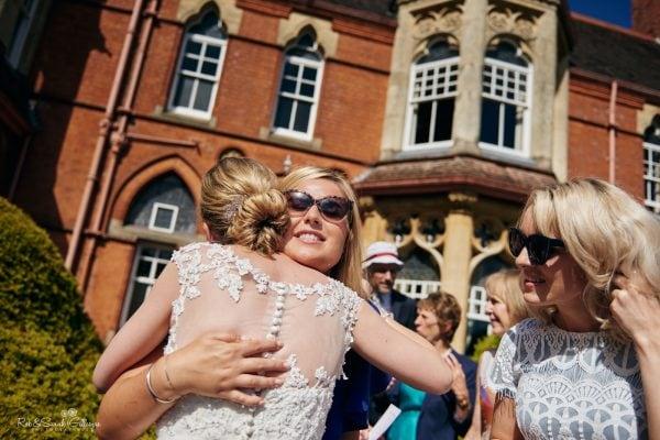 Wedding guest hugs bride outside Highbury Hall on a sunny day