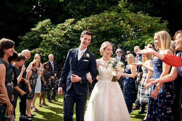 Bride and groom walk through confetti