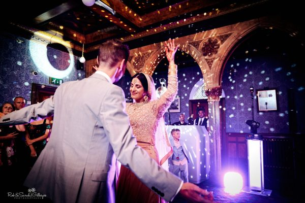 Bride in Indian wedding dress and groom dancing at Highbury Hall, with coloured lights