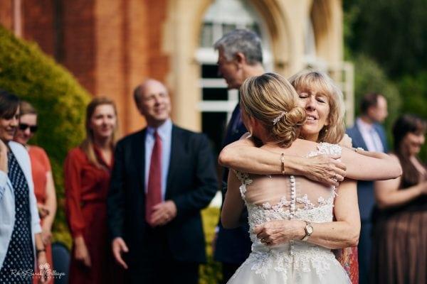 Wedding guest hugs bride