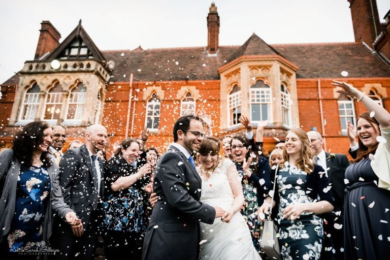 Bride and groom have confetti thrown over them by laughing guests with Highbury Hall in background