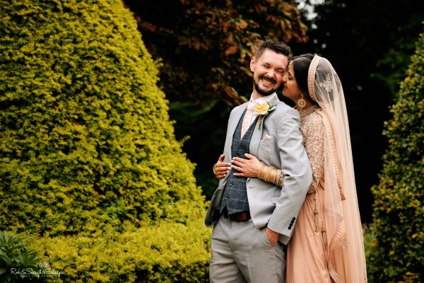 Bride in Indian wedding dress puts arms around groom in gardens