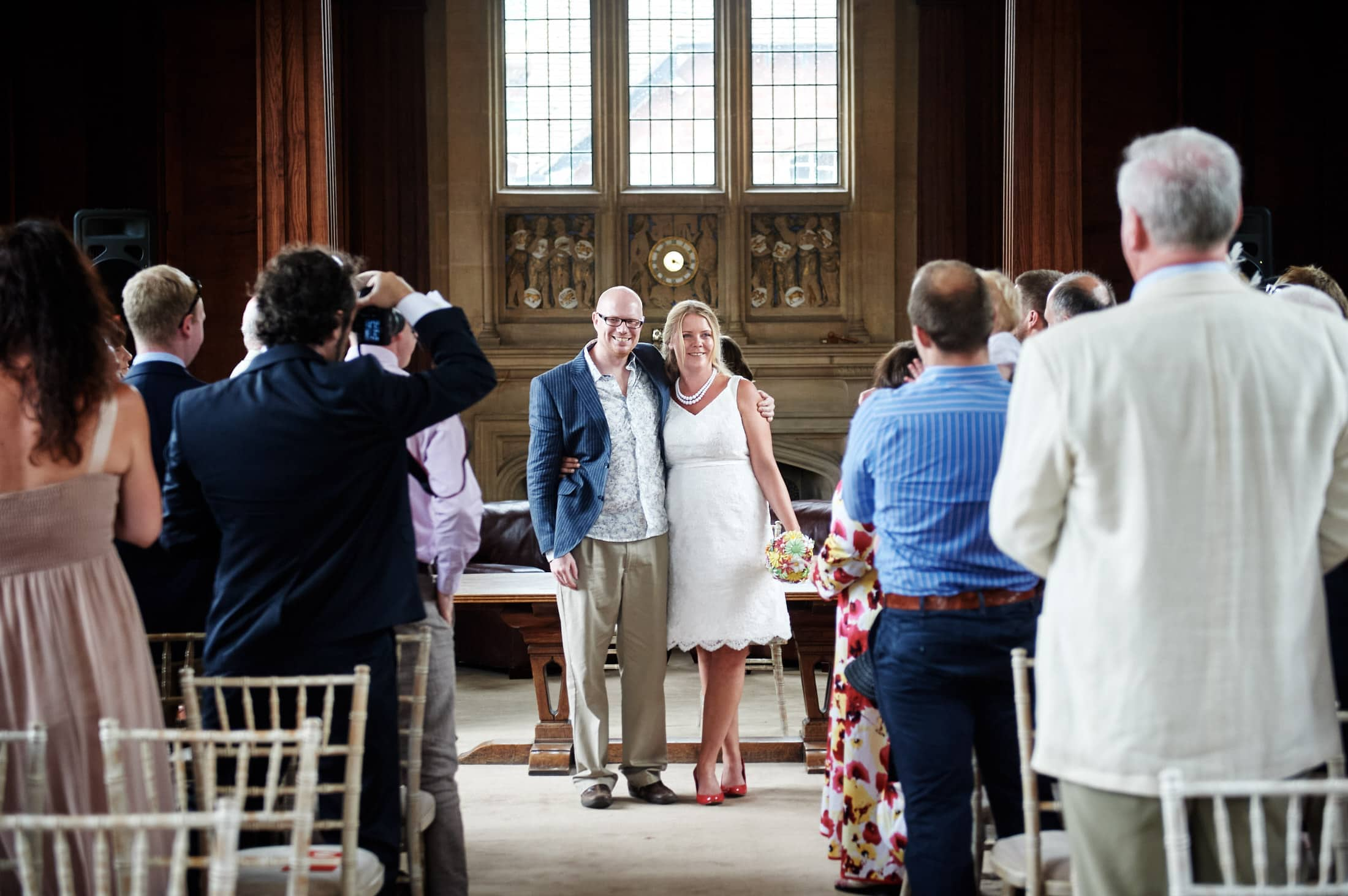 Bride and groom pose as guests take photos during wedding ceremony in Memorial Library at Malvern College
