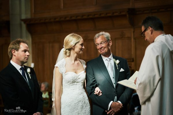 Father smiles at daughter during wedding ceremony in chapel at Malvern College