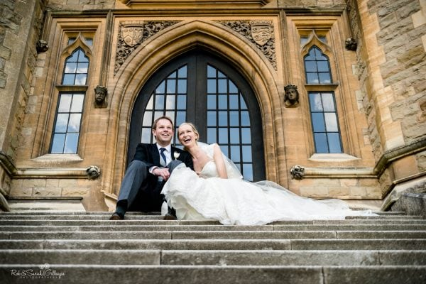 Bride and groom laughing while sitting on steps at Malvern College