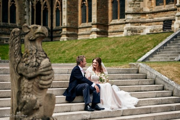 Bride and groom sitting on stone steps at Malvern College with griffin statue in foreground