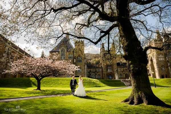 Bride and groom walk through beautiful grounds at Malvern College on sunny day