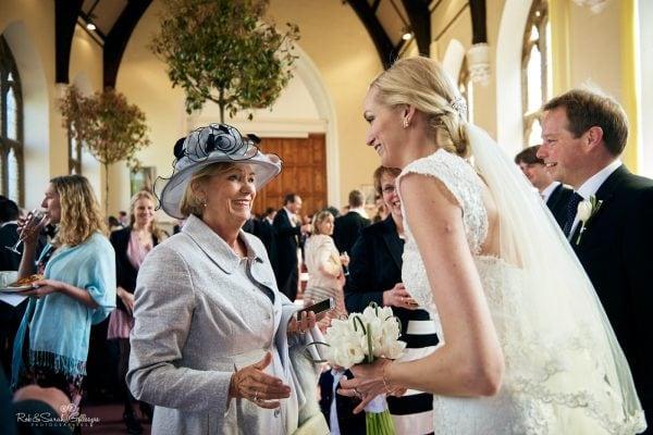 Bride and mother talk during wedding reception in Big School room at Malvern College