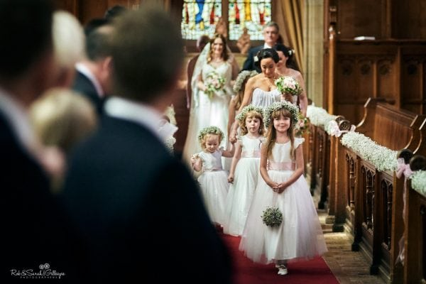 Flowergirls and bridesmaids make their entrance to wedding ceremony