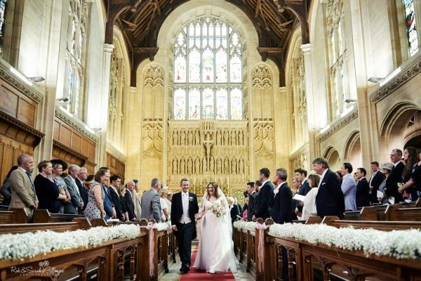Bride and groom walk out of wedding ceremony in chapel at Malvern College