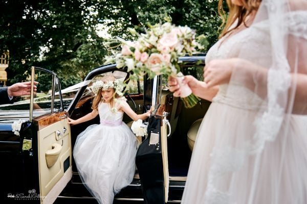 Flowergirl jumps out of wedding car with bride in foreground