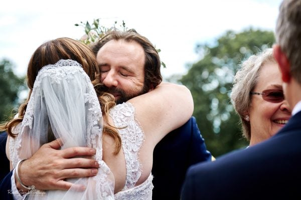 Wedding guest hugs bride with eyes closed