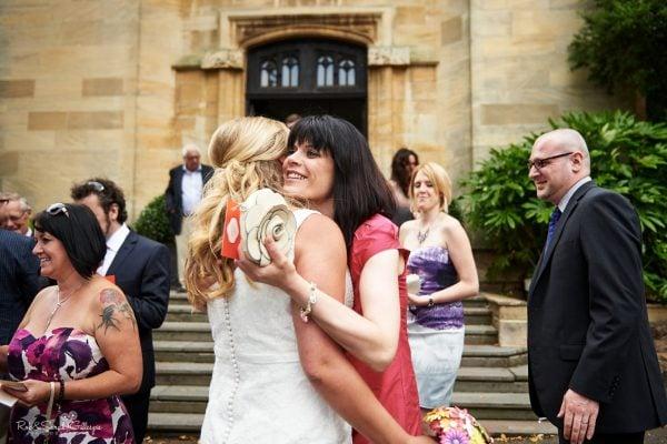 Wedding guest hugs bride outside Malvern College Memorial Library
