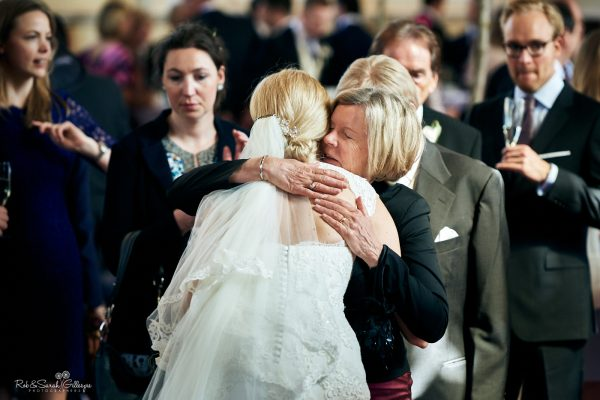 Wedding guest hugs bride during wedding reception