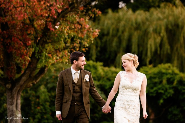 Bride and groom walk hand in hand through Pendrell Hall grounds with apple tree in background
