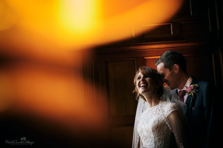 Bride and groom laughing in window light with orange light from lamp in foreground