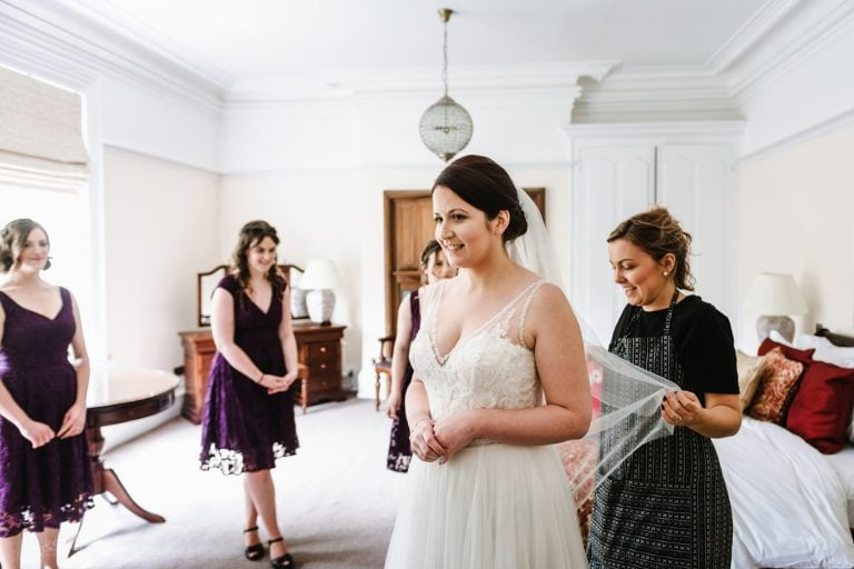 Bride has veil fitted in bedroom at Pendrell Hall as bridesmaids watch