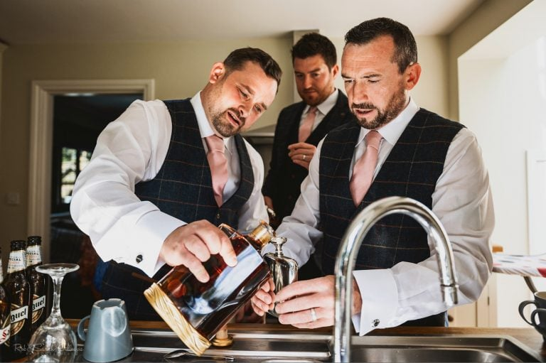 Groomsmen pour brandy while preparing for wedding at Pendrell Hall