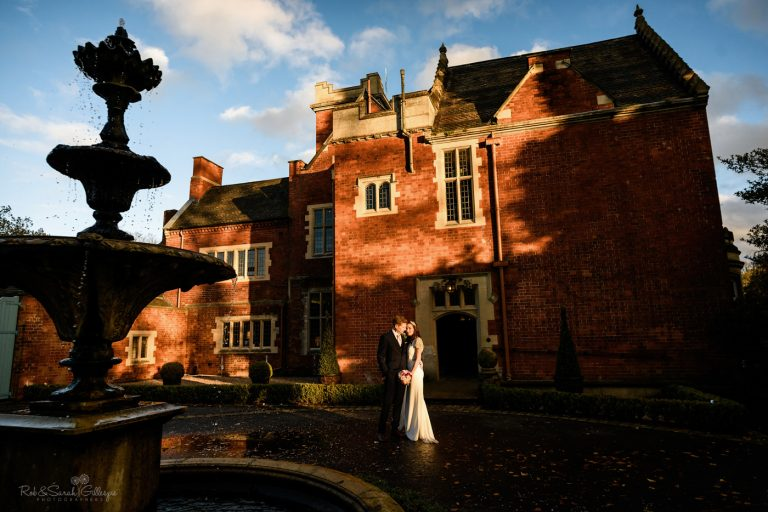 Bride and groom in beautiful winter light at front of Pendrell Hall wedding venue