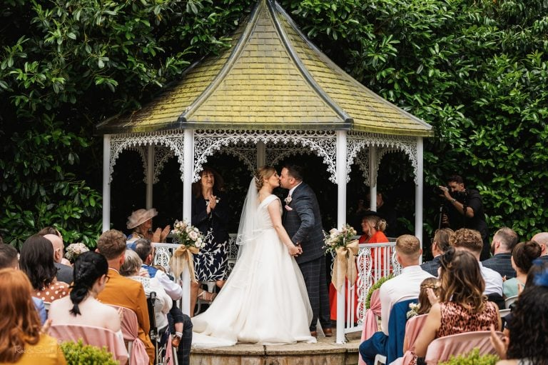 Bride & Groom kiss during outdoor wedding ceremony at Pendrell Hall
