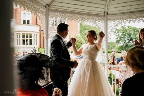 Bride punches air during outdoor wedding ceremony at Pendrell Hall