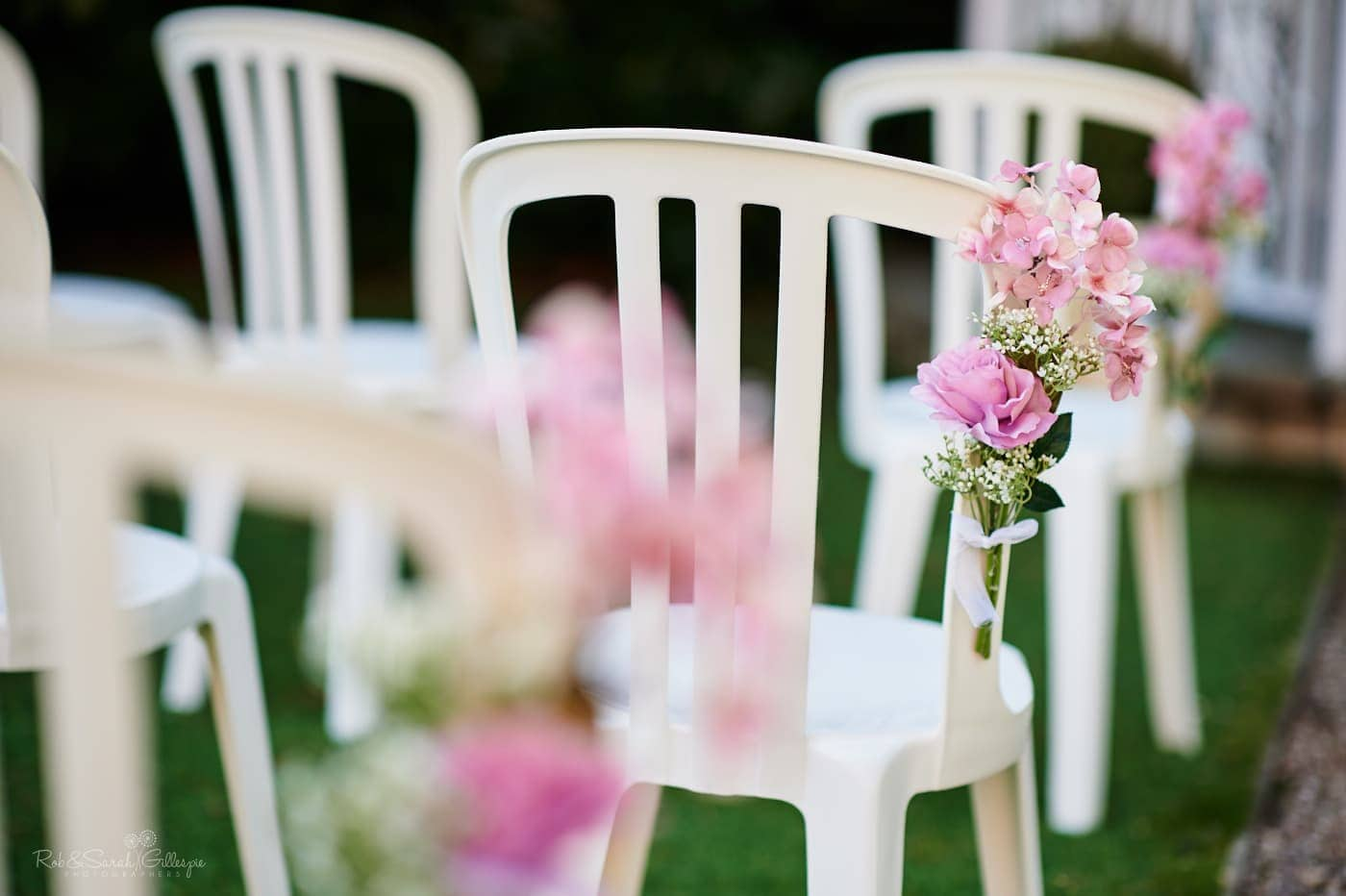 Pink flowers tied to white chairs ready for outdoor wedding ceremony