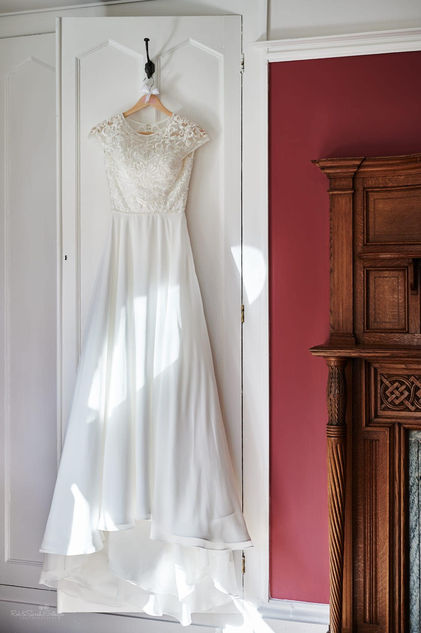 White wedding dress handing in Strawberry Thief room at Pendrell Hall