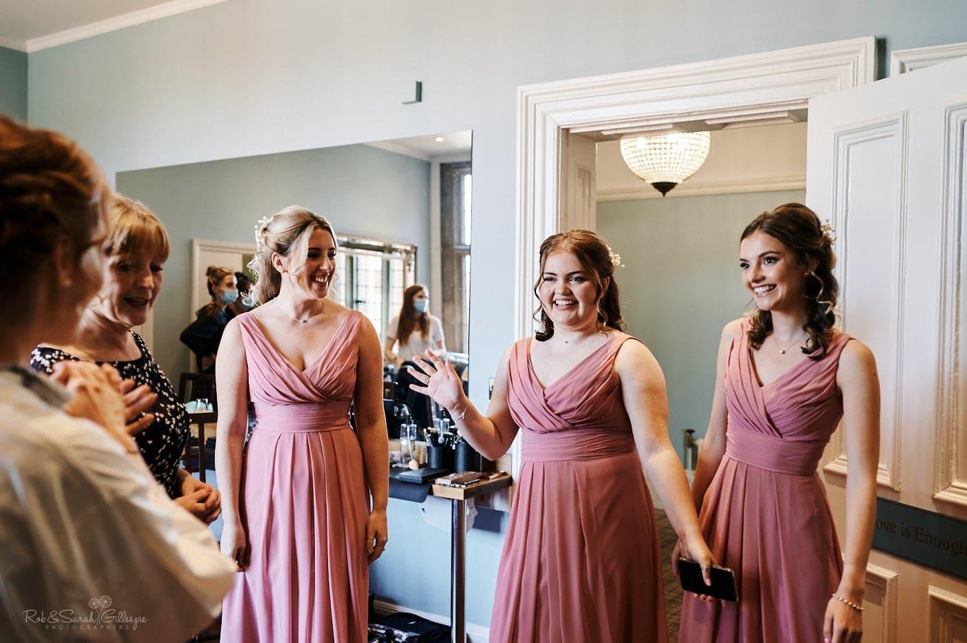 Bridesmaids show off their dresses to bride