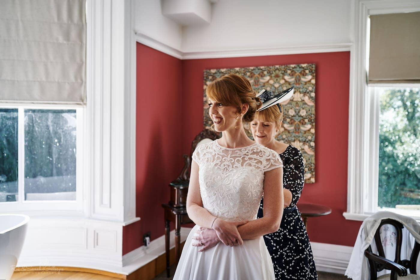 Bride's mum helps her into wedding dress in Strawberry Thief room at Pendrell Hall