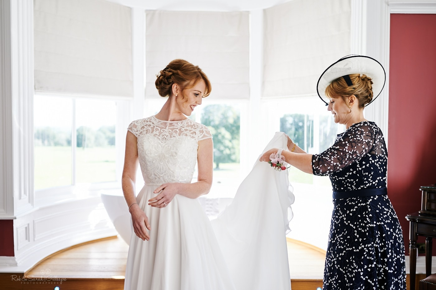 Bride and her mother adjust wedding dress in front of large window