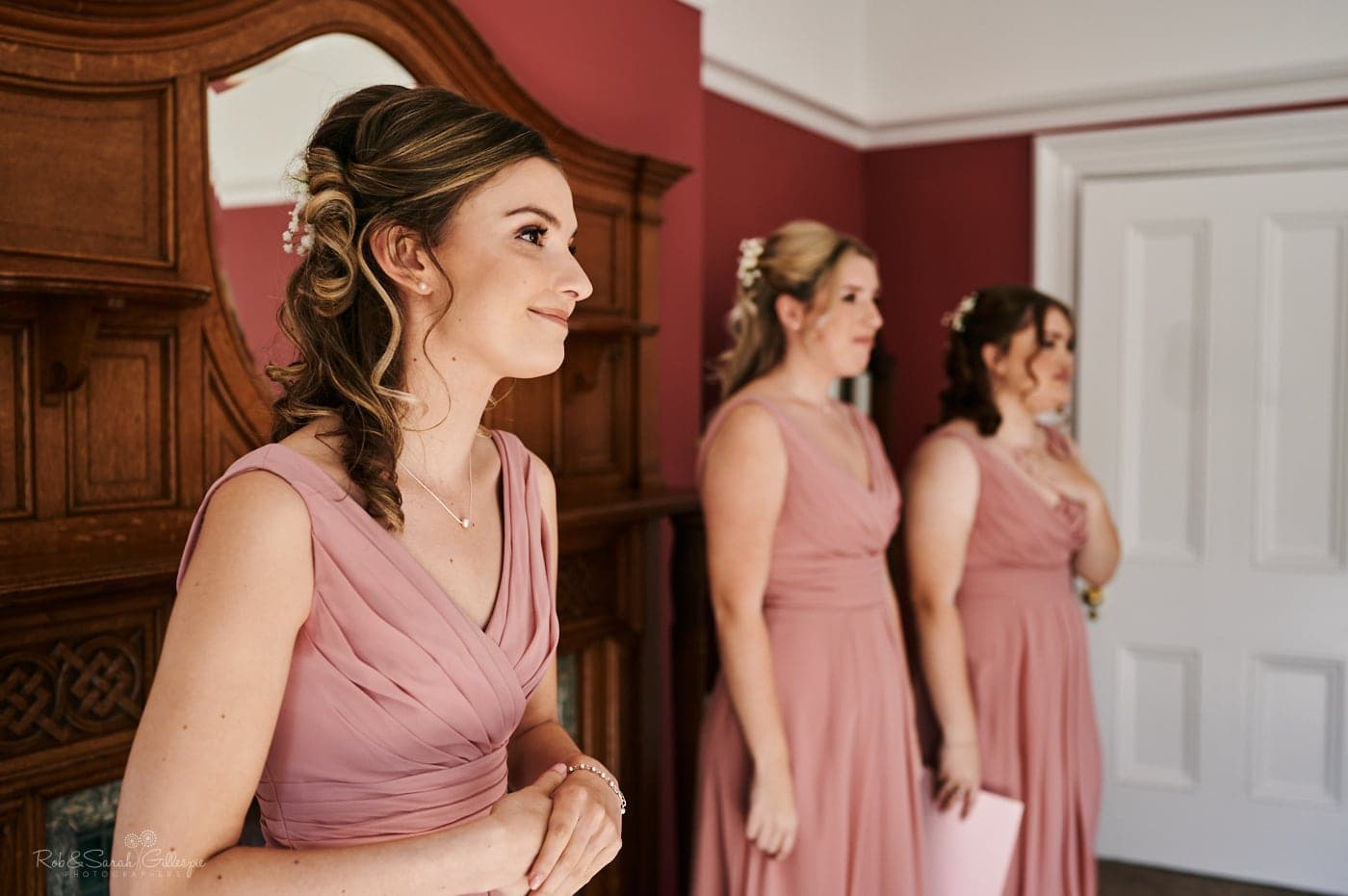 Bridesmaids watch and smile as bride gets into her wedding dress