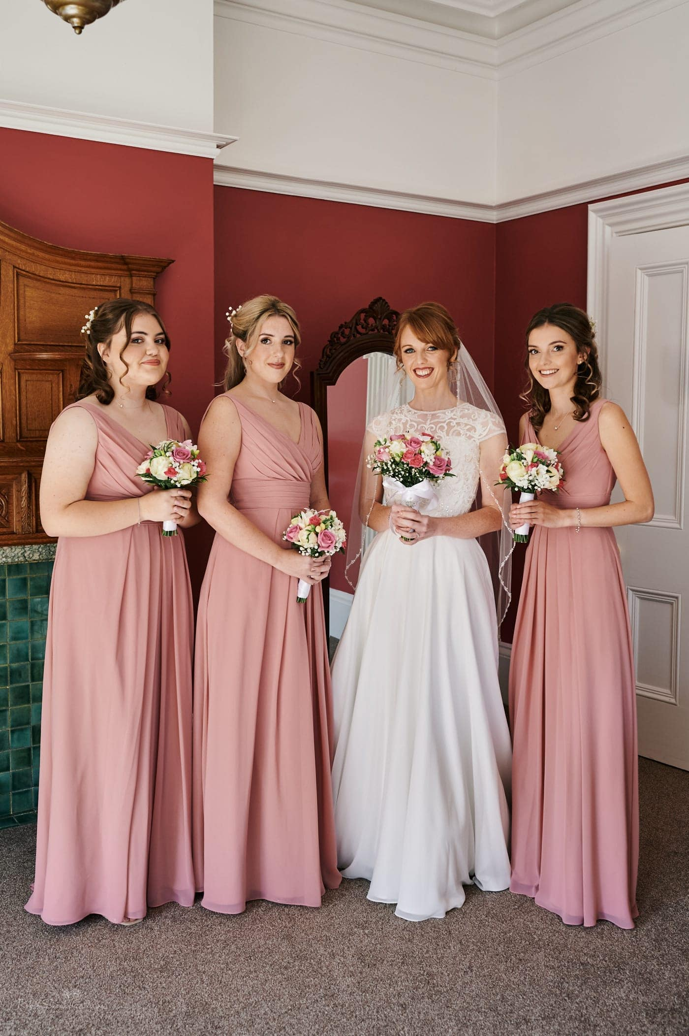 Group photo of bride and bridesmaids in Strawberry Thief room at Pendrell Hall