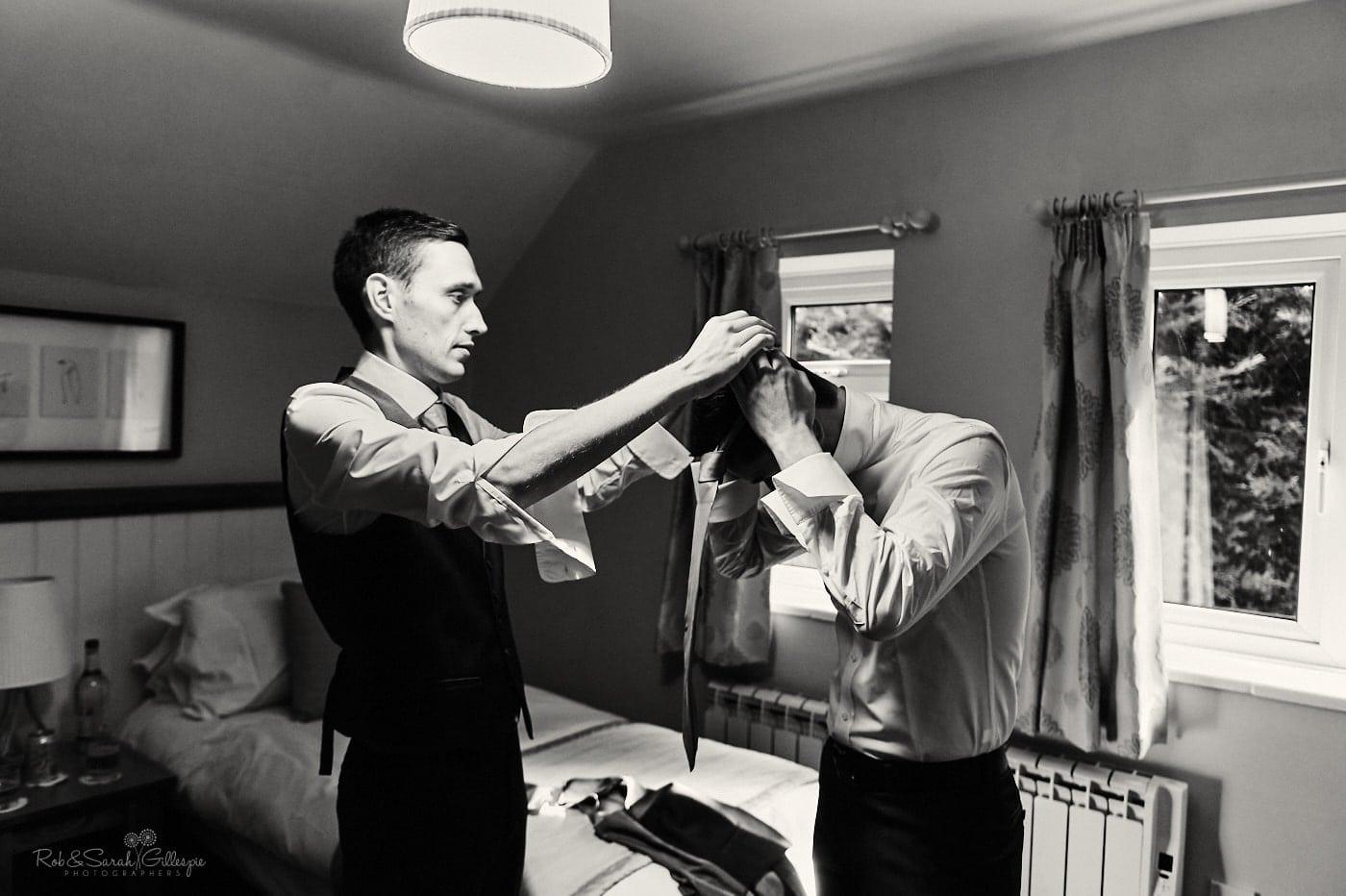 Groom helps best man fix tie