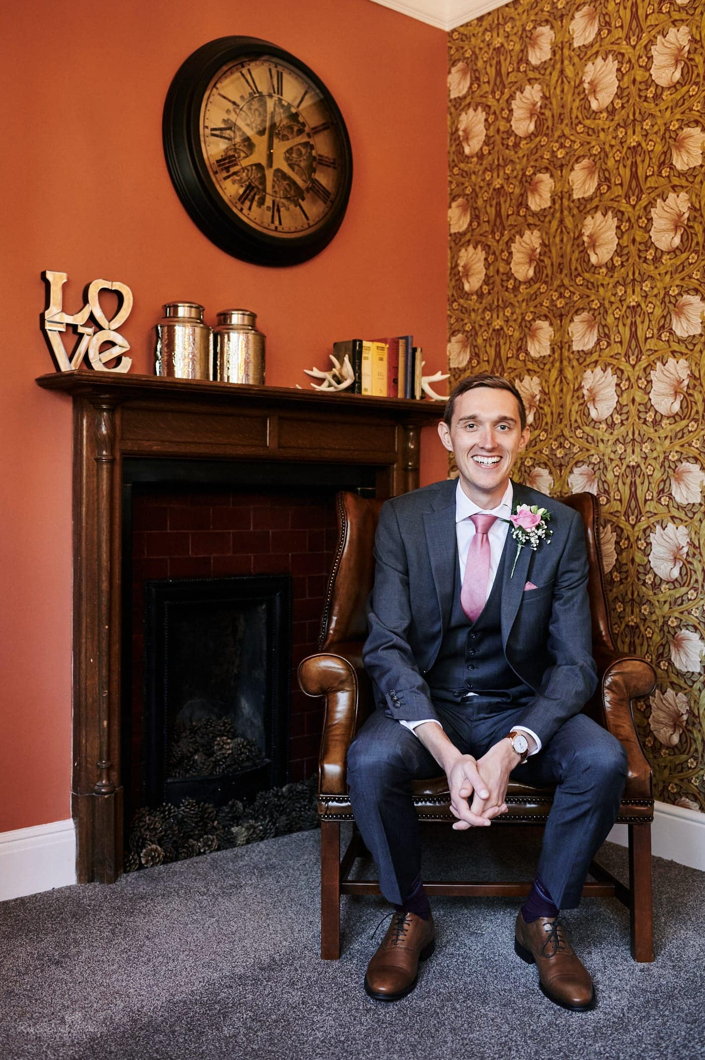 Portrait of groom sitting in Pimpernel Suite at Pendrell Hall