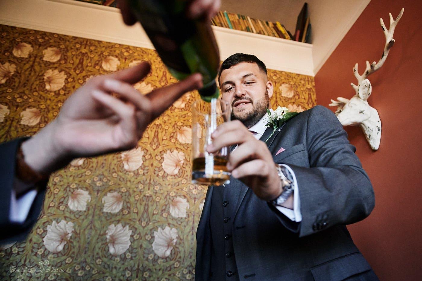 Groosman has drink poured as her prepares for wedding
