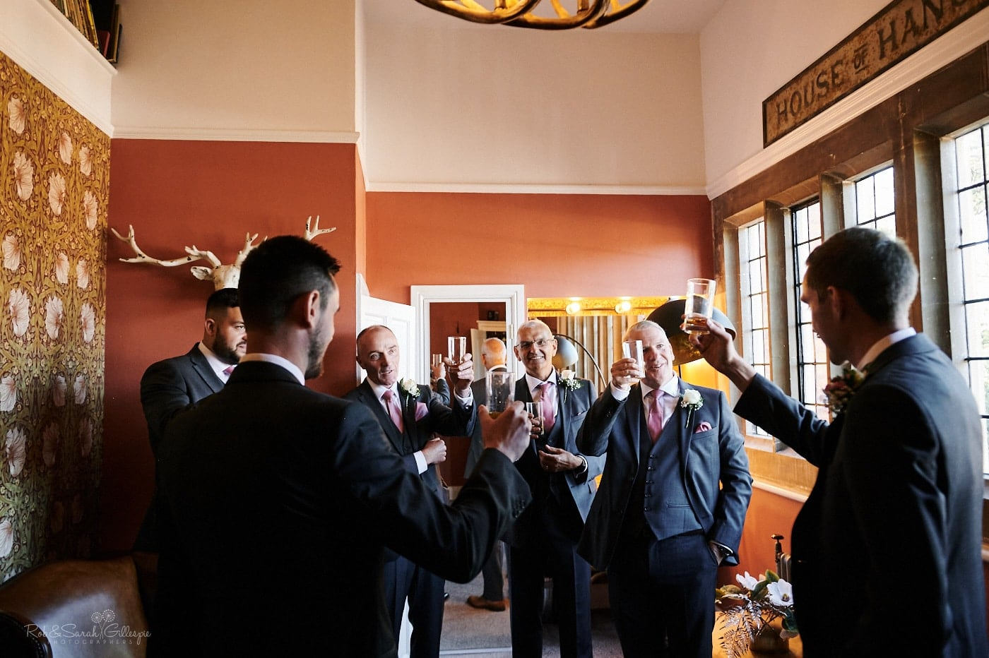 Groomsmen raise toast together in Pimpernel Suite at Pendrell Hall
