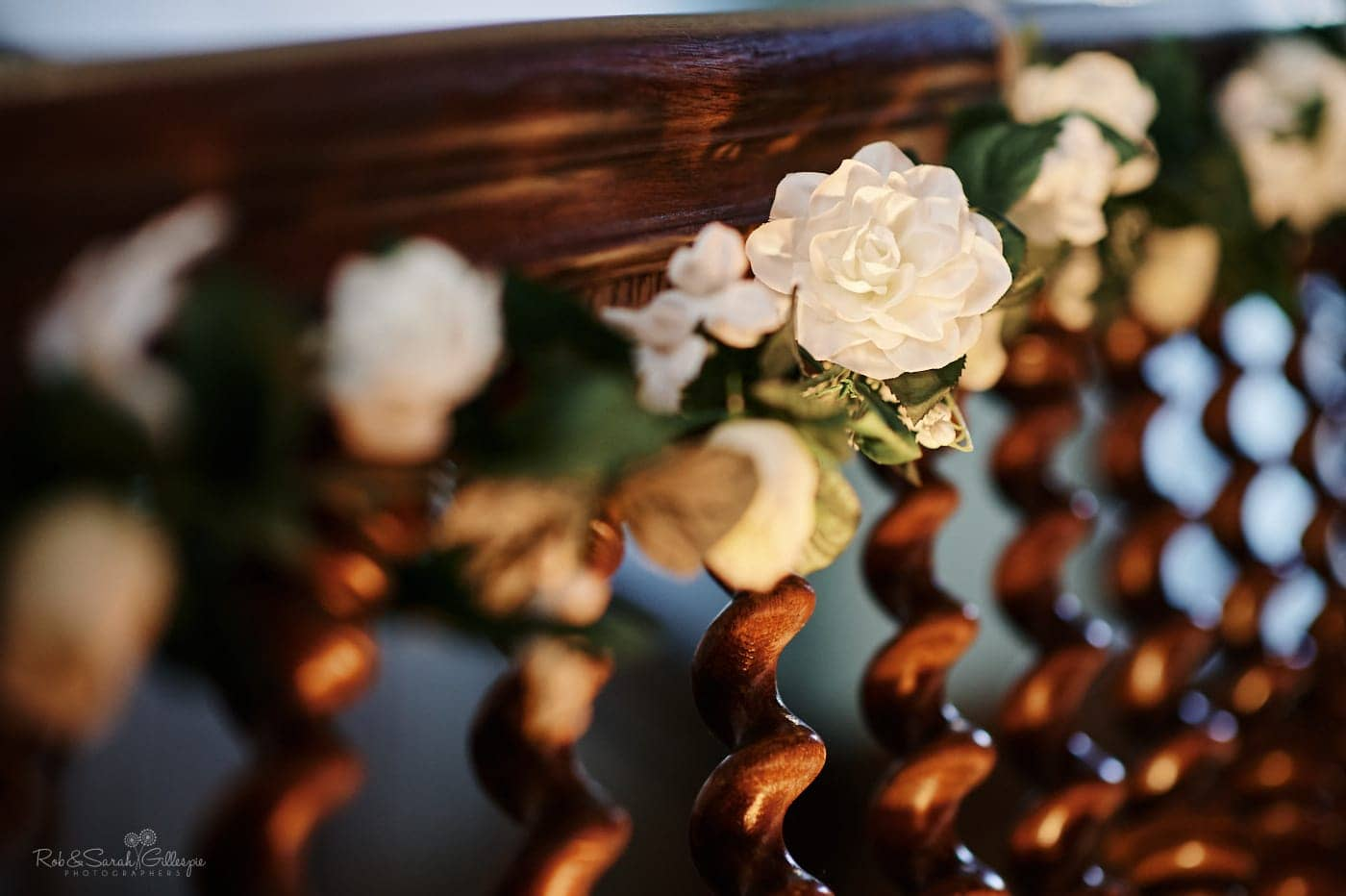 White flowers attached to wooden bannister rail