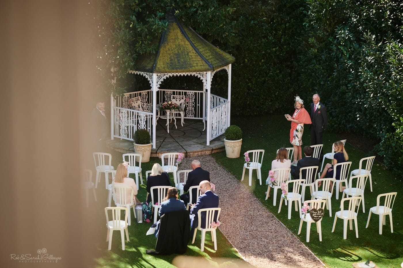 Wedding guests arrive and take their seats for outdoor ceremony in gardens at Pendrell Hall