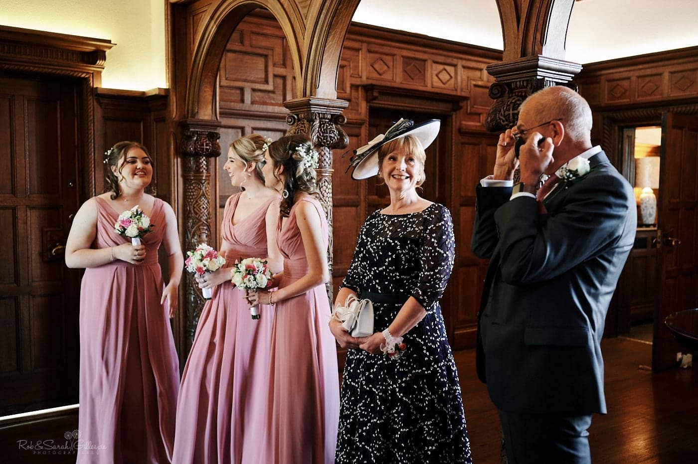 Bridesmaids and parents wait for bride in beautiful wood-panelled room at Pendrell Hall