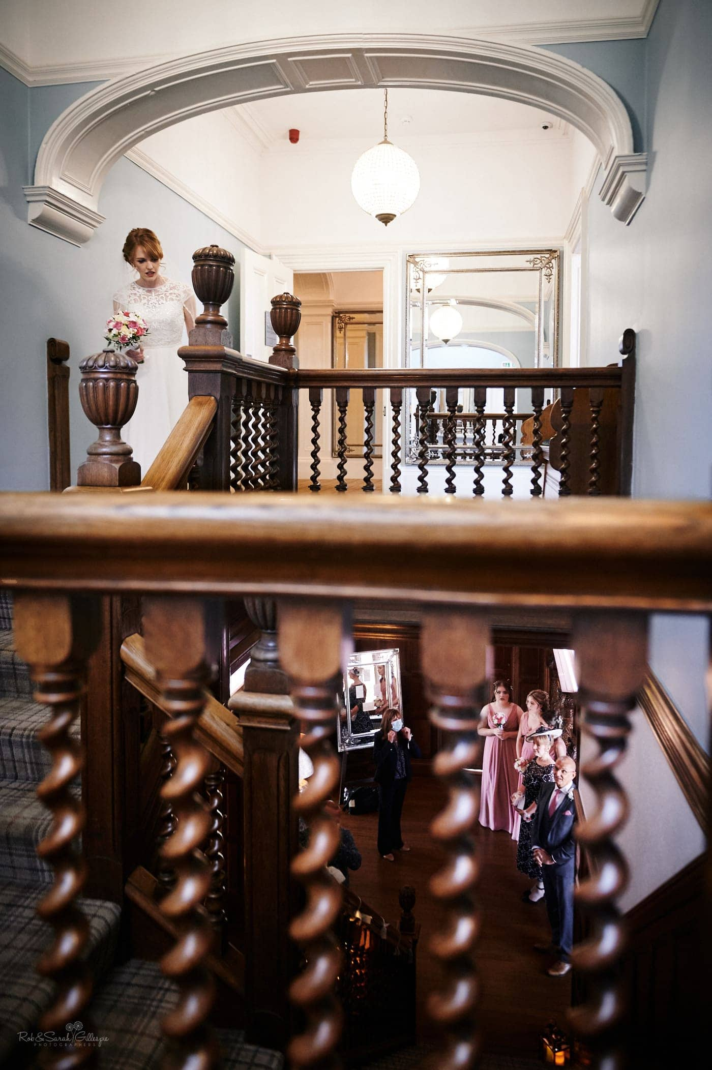 Bride peeks downstairs at bridesmaids