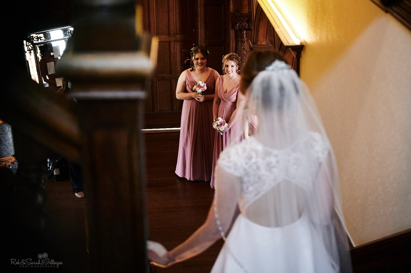 Bridesmaids watch as bride descends staircase at Pendrell Hall