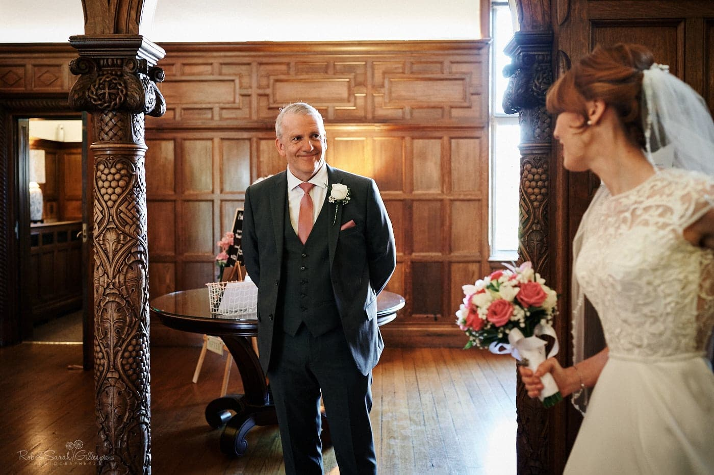 Bride's father smiles at her as he sees her in wedding dress for first time