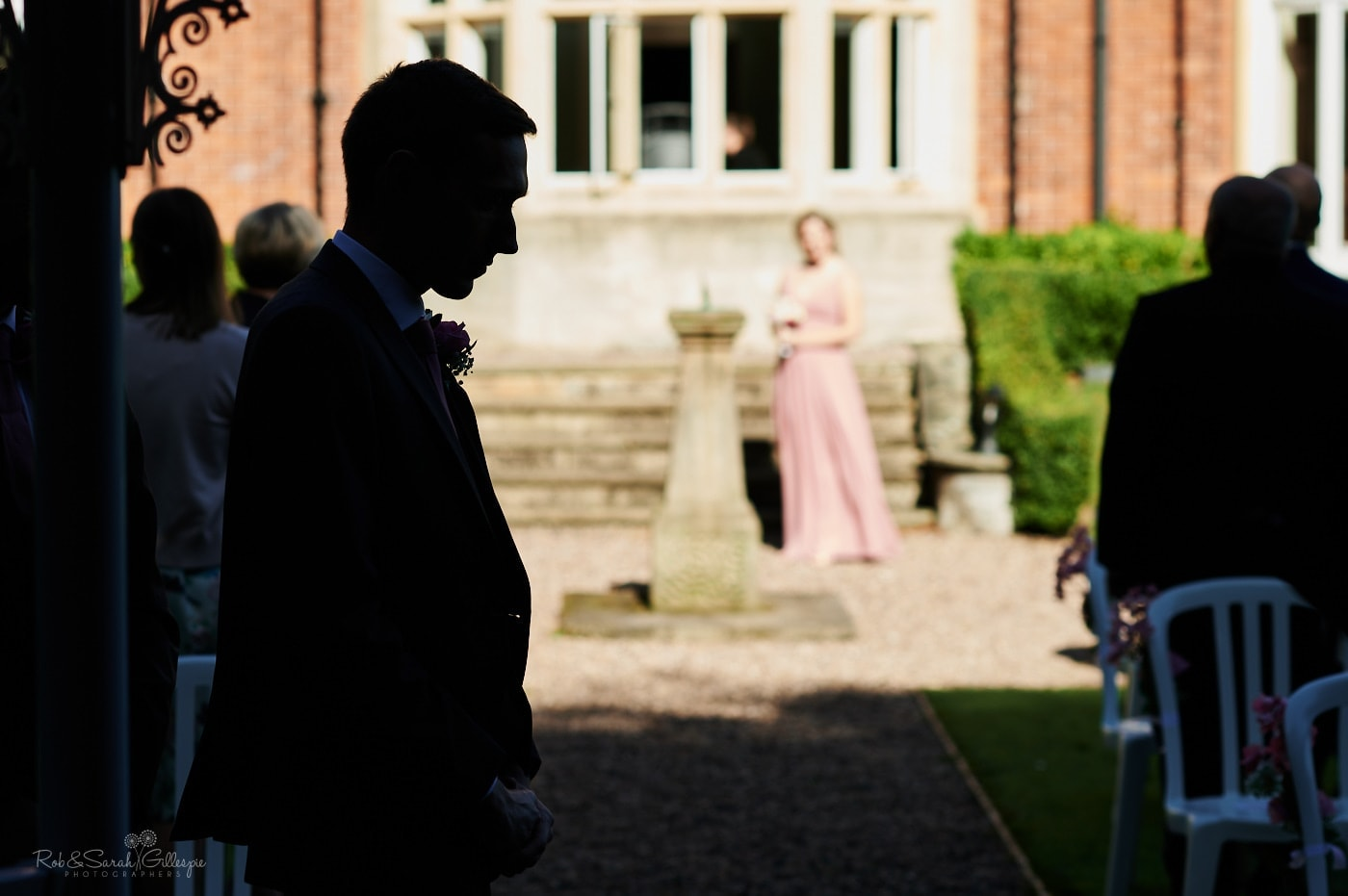 Groom in silhouette as he waits for outdoor wedding ceremony to start at Pendrell Hall