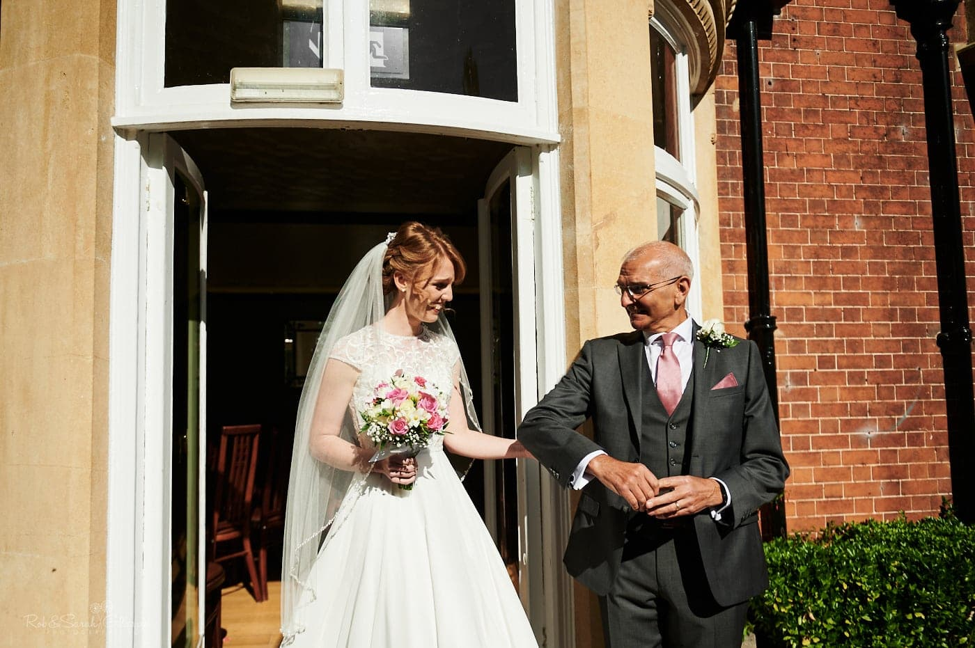 Bride and father make their way to outdoor ceremony with small number of guests
