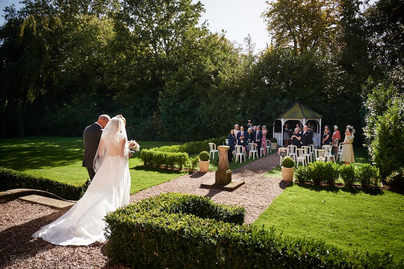 Bride and father walk up aisle for outdoor wedding ceremony at Pendrell Hall as guests watch