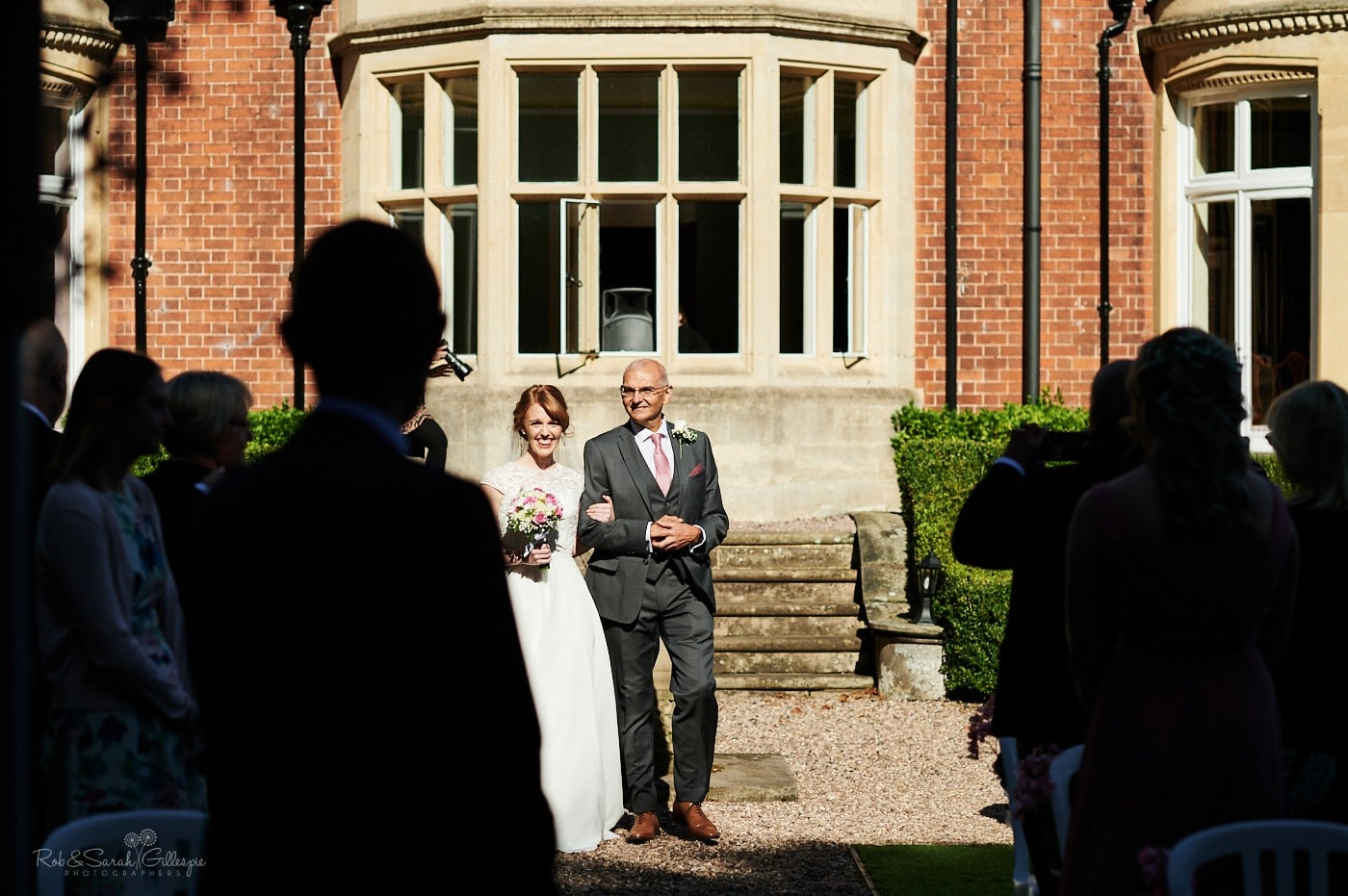 Bride and father walk up aisle in bright sunshine