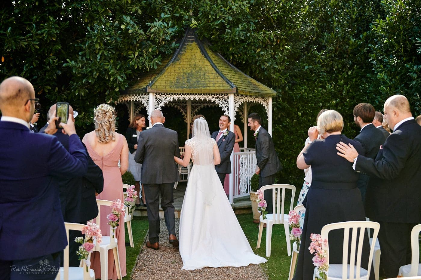 Groom smiling as bride walks up aisle during outdoor wedding ceremony at Pendrell Hall